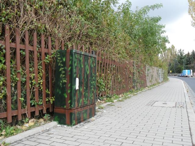 Brauner Gartenzaun vor der Hecke, angepasst an denn Hintergrund