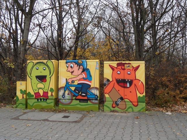 Grünes Monster auf Inlinern, Junge auf Fahrrad, Orangenfarbenes Monster mit Skateboard