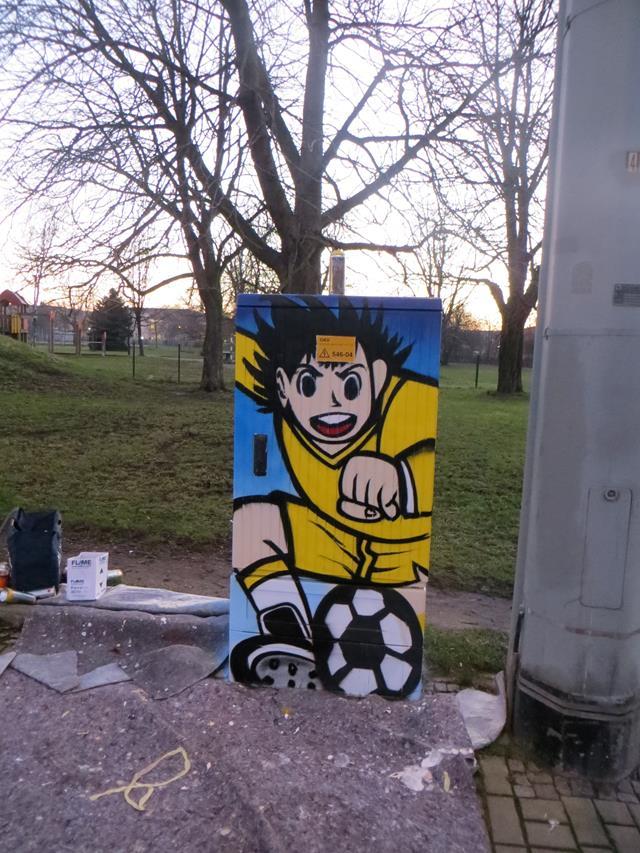 Vorderseite: Fußball spielender Junge im gelben Trikot