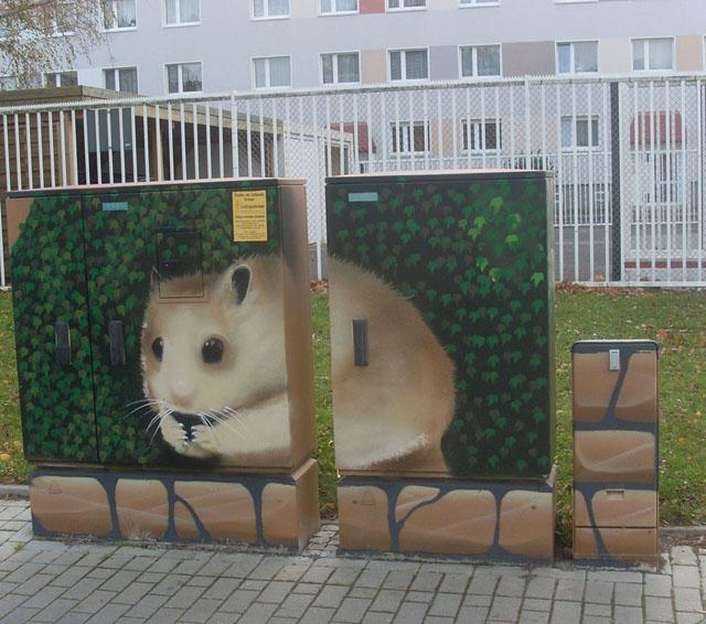Ein Hamster sitzt vor einem Busch, der vor einer Mauer steht
