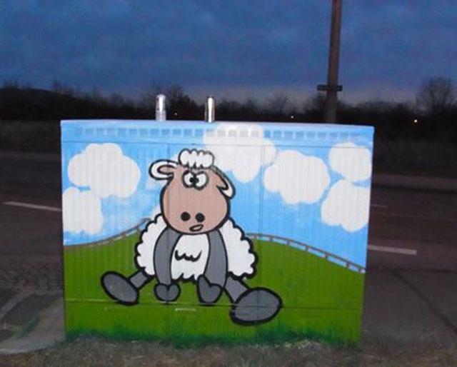 Rückseite: Schaf sitzt auf der Wiese